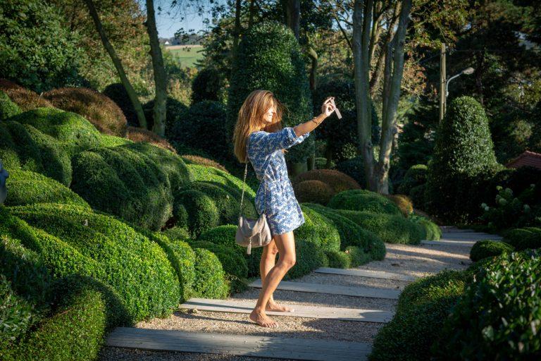 Une femme prend une photo dans les Jardins d'Etretat