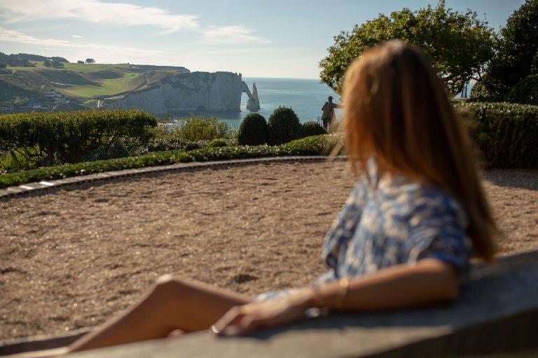 Une femme installée sur un banc profite du cadre et de la vue depuis les Jardins d'Etretat