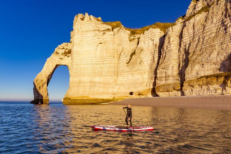 Un enfant en paddle le long des falaises d'Etretat