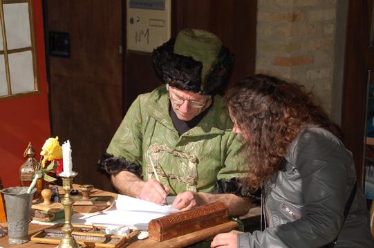 Artisan en costume médiéval, entrain d'écrire alors qu'une personne le regarde
