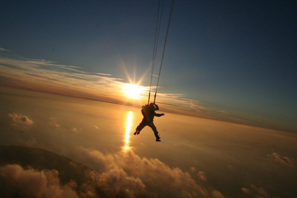 Saut en parachute avec le coucher de soleil