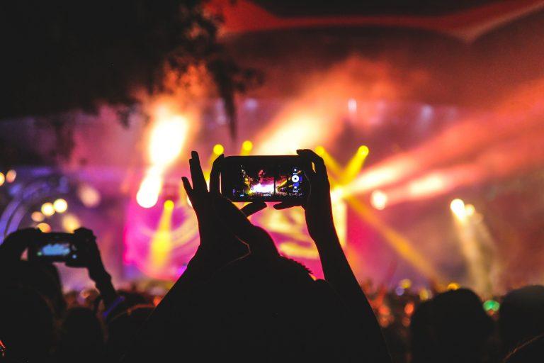 Personne utilisant son smartphone pour filmer un spectacle de nuit en extérieur