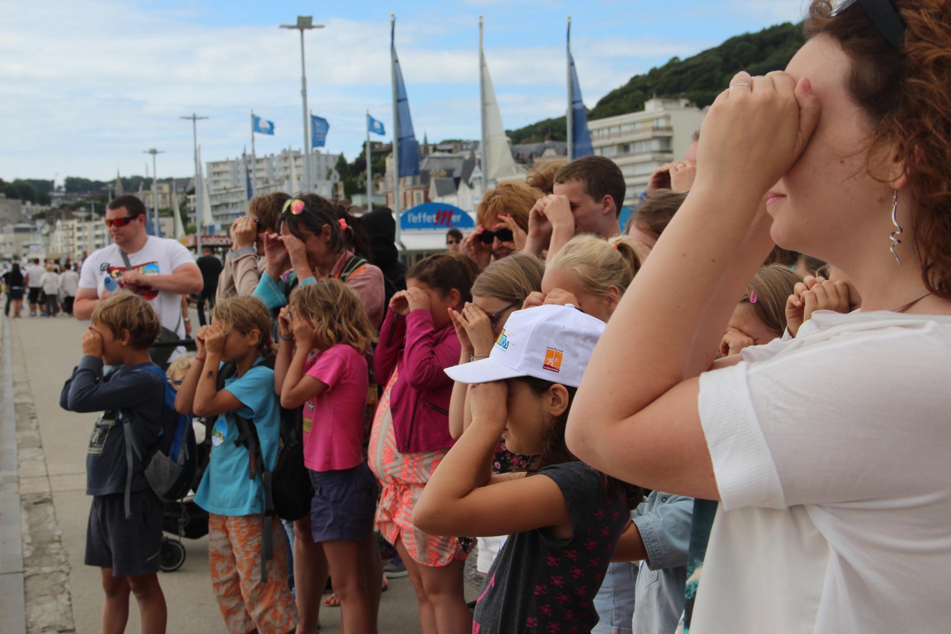 Groupe de plusieurs famille regardant vers la mer, devant les restaurants de la plage