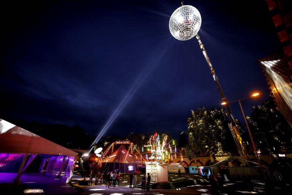 Ouest Park Festival, extérieur avec une boule à facettes géante, un chapiteau, et un arbre illuminé