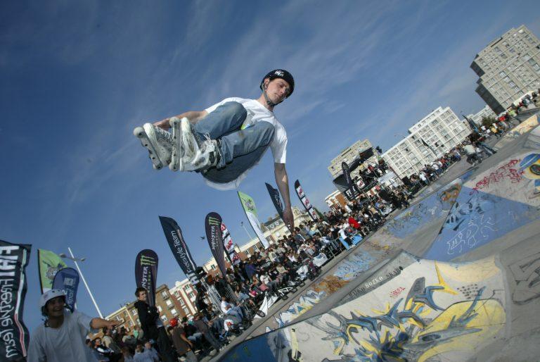 Homme à rollers réalisant une figure acrobatique dans le skatepark