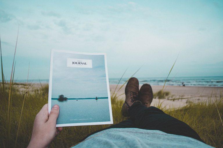 Homme sur la plage tenant une brochure