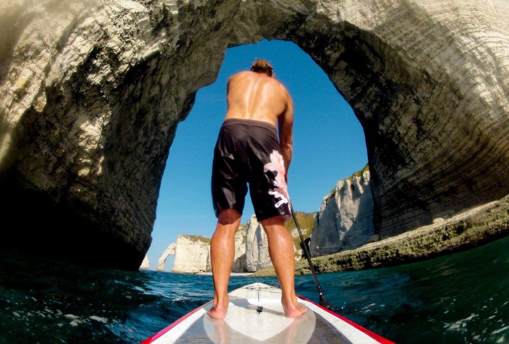 Homme sur un paddle sous l'arche d'Etretat